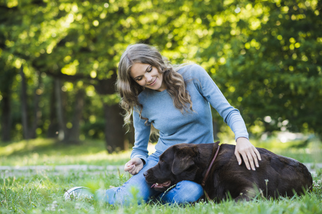 woman with a dog in the garden. woman is preparing to trim dog nails that are over grown