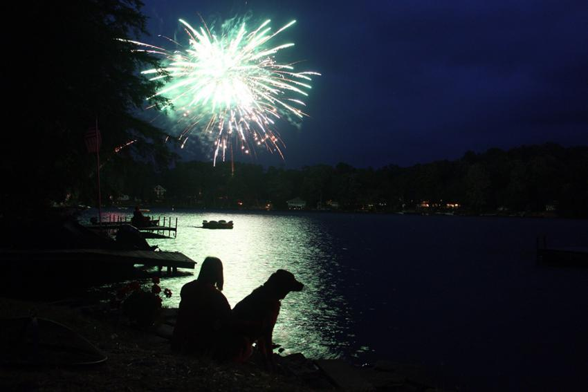 woman and her dog sitting on a lake. A dog scared of fireworks