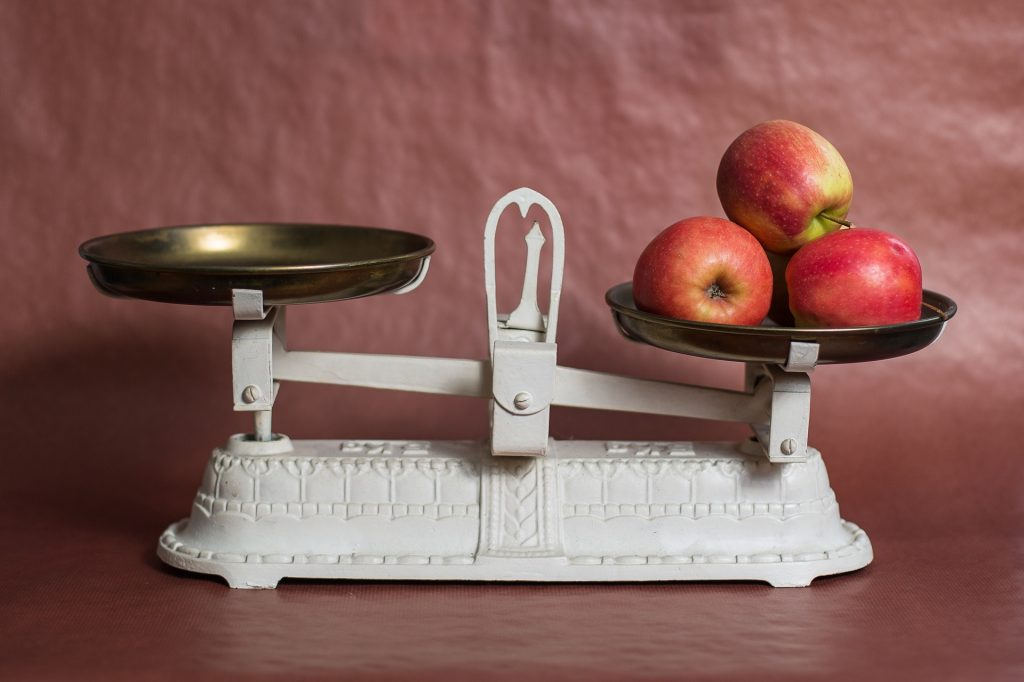 white scale with two plates on it, one of them has apples in it