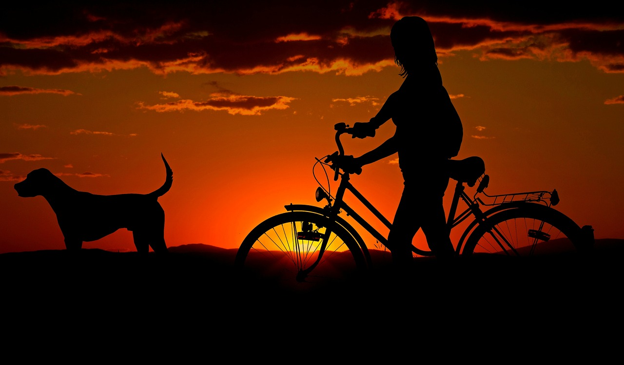 A lady with a bike and a dog